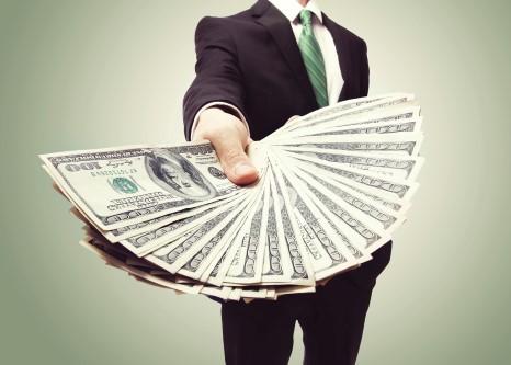 הלוואות פרטיות - איש עסקים שולח יד עם דולרים