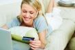 אשה שוכבת על ספה מול לפטופ ומחלקת את תשלום האשראי שלה