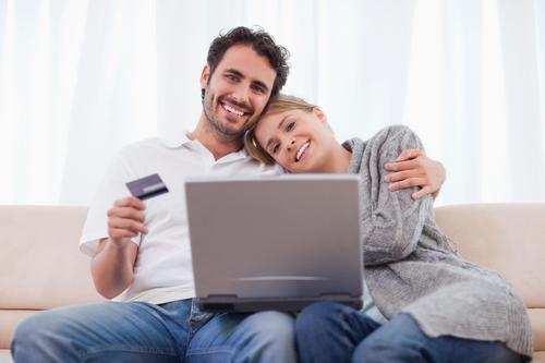 זוג יושב מול לפטופ ומחזיק ביד כרטיס אשראי